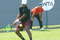 Donald Young hits an under pressure backhand