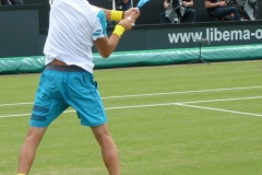 Evgeny Donskoy hits a backhand return