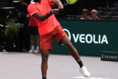 Frances Tiafoe hits a high backhand
