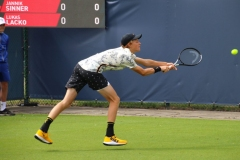 Jannik Sinner reaching for a backhand return