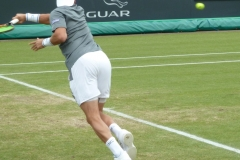 Malek Jaziri reaches to serve down the middle