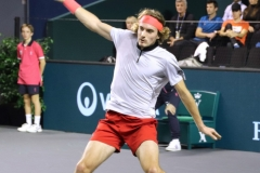 Stefanos Tsitsipas hits a backhand  with his coach/dad watching in the background