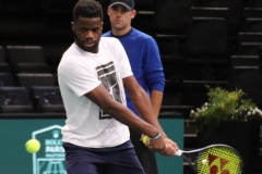 Frances Tiafoe hits a backhand while Robby Ginepri watches in the background